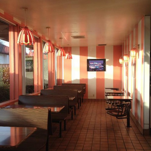 Indoor seating area of Bob's Footlongs with tables and pink and white striped wall