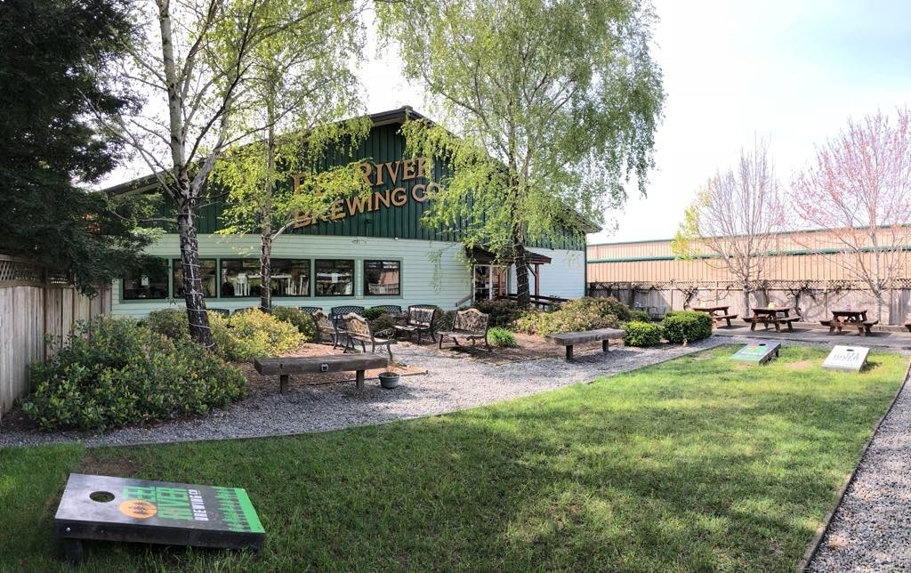 Eel River Brewing Company outdoor seating area with garden area, benches, and cornhole